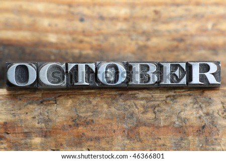 the word october in letterpress type on a wooden background. - stock photo