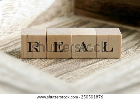 the word of REAL on wooden cubes