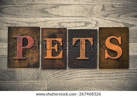 """The word """"PETS"""" theme written in vintage, ink stained, wooden letterpress type on a wood grained background. - stock photo"""