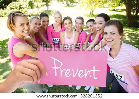 The word prevent and hand holding card against smiling women running for breast cancer awareness - stock photo