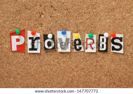 The word Proverbs, one of the books of the Holy Bible in cut out magazine letters pinned to a cork notice board