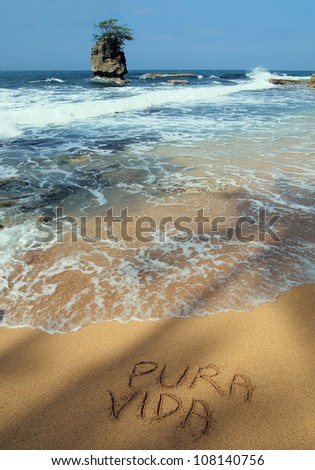 """The word """"pura vida"""" written on the sand in a tropical beach with rocky islet, Caribbean, Costa Rica - stock photo"""