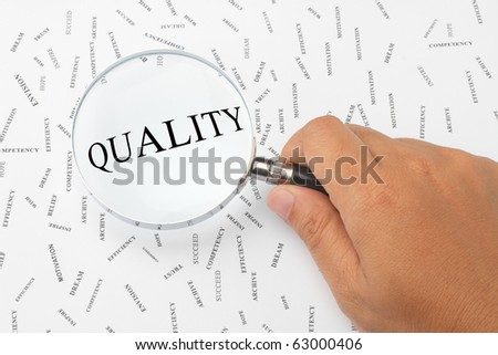 The word, QUALITY is magnified. - stock photo