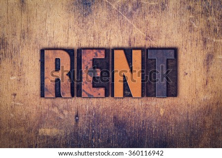 """The word """"Rent"""" written in dirty vintage letterpress type on a aged wooden background. - stock photo"""