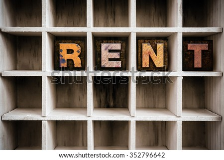 """The word """"RENT"""" written in vintage ink stained wooden letterpress type in a partitioned printer's drawer. - stock photo"""