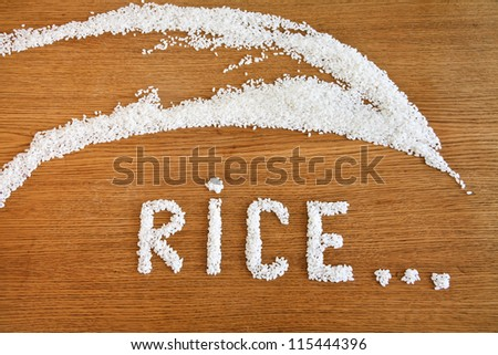 The word 'rice' written in rice on a wooden table