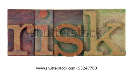 the word risk in vintage wooden letterpress type blocks, stained by color ink, isolated on white - stock photo