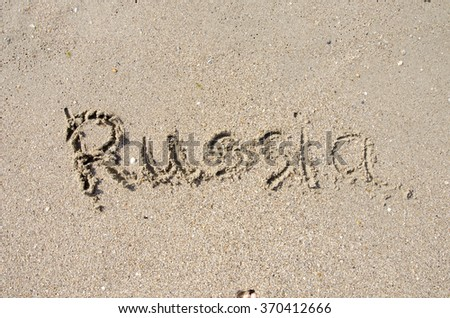 The word Russia handwritten in sand on a beach, ideal for internet or conceptual designs background with feet metaphor for communication, speech, message, mail, dialog, talk, contact, email, internet
