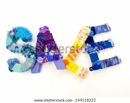 """the word """"sale"""" created with brightly colored knitting yard - stock photo"""