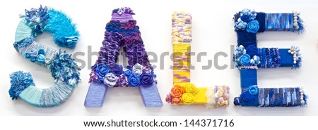 "the word ""sale"" created with brightly coloured knitting yard - stock photo"