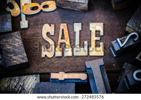 The word SALE written in rusted metal letters surrounded by vintage wooden and metal letterpress type. - stock photo