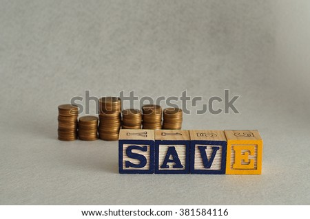 The word Save spelled with colorful alphabet blocks and stacks of coins in the back that is out of focus - stock photo