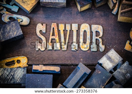 The word SAVIOR written in rusted metal letters surrounded by vintage wooden and metal letterpress type. - stock photo
