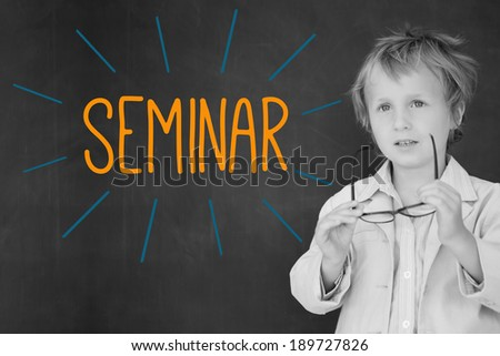 The word seminar against schoolboy and blackboard - stock photo