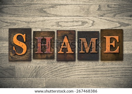 "The word ""SHAME"" theme written in vintage, ink stained, wooden letterpress type on a wood grained background. - stock photo"