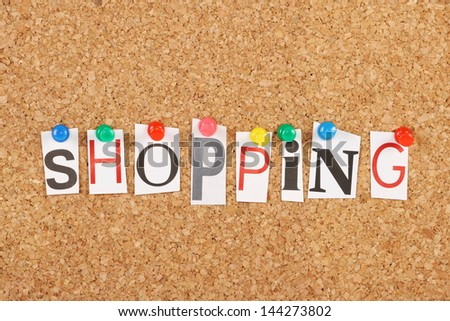 The word Shopping in cut out magazine letters pinned to a cork notice board