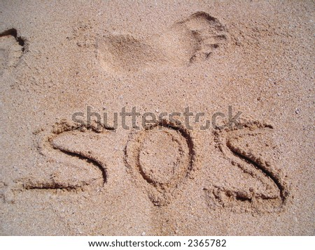 The word sos written on a sandy beach in bold. - stock photo