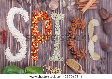 """The word """"spices"""" written with Different  spices  on a wooden background - stock photo"""