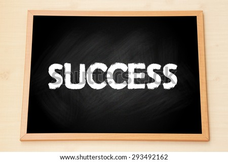 The word 'Success' on black chalkboard with wooden frame on wood background. - stock photo