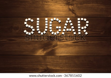The word 'sugar', built from white cubes pieces of sugar on background  of panel from vintage wooden boards brown color in high contrast dramatic lighting  'Hard light' - stock photo