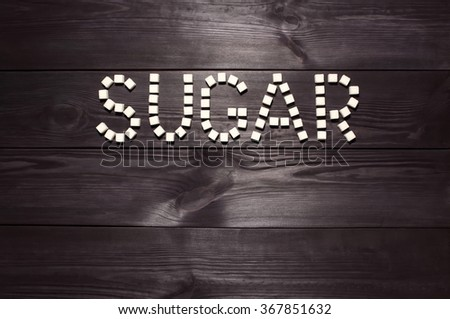 The word 'sugar', built from white cubes pieces of sugar on background  of panel from vintage wooden boards black color in high contrast dramatic lighting  'Hard light' - stock photo