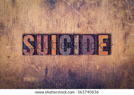 """The word """"Suicide"""" written in dirty vintage letterpress type on a aged wooden background. - stock photo"""
