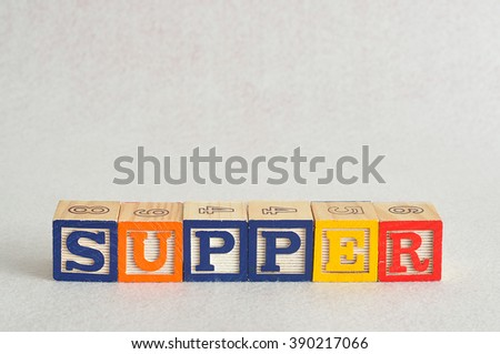 The word supper spelled with alphabet blocks isolated on a white background - stock photo