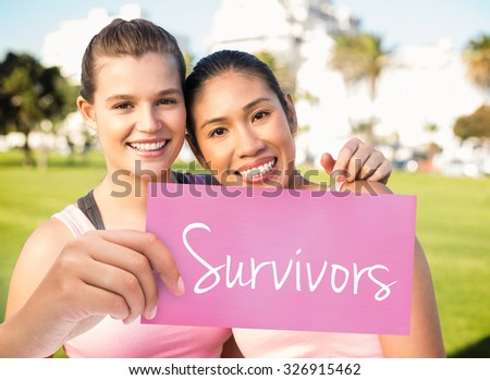 The word survivors and hand holding card against two smiling women wearing pink for breast cancer - stock photo