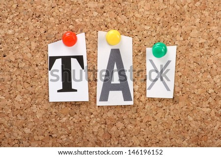 The word tax in cut out magazine letters pinned to a cork notice board