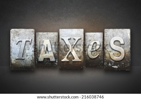 The word TAXES written in vintage letterpress type - stock photo