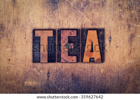 """The word """"Tea"""" written in dirty vintage letterpress type on a aged wooden background. - stock photo"""