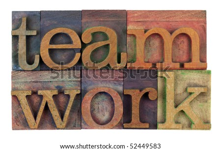 the word teamwork in vintage wooden letterpress type, stained by colorful inks, isolated on white