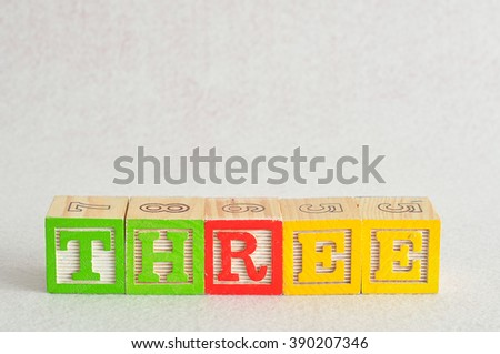 The word three (3) spelled with colorful alphabet blocks isolated against a white background - stock photo