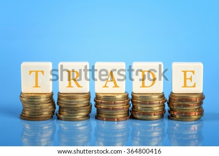 The word Trade on stacked coins, finance conceptual