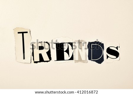 the word trends written with different letters made of clippings of newspapers and magazines, on an off-white background - stock photo