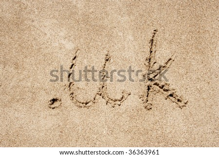 The word .uk handwritten in sand on a beach, ideal for internet or conceptual designs