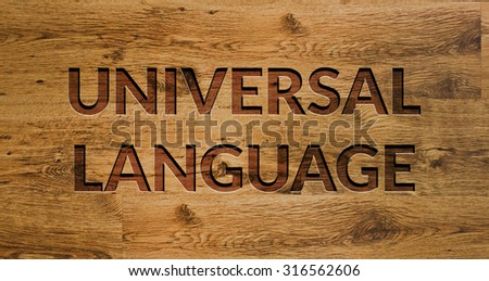 The word UNIVERSAL LANGUAGE Engraved in Wooden Background. - stock photo