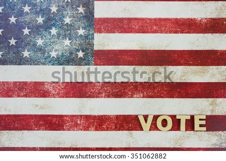 The word VOTE on antique rustic American canvas flag in background - stock photo