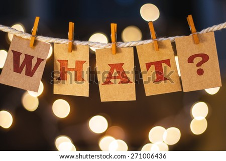 The word WHAT? printed on clothespin clipped cards in front of defocused glowing lights. - stock photo