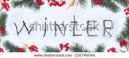 The word winter written with broken wooden sticks on snow background inside berries fir branch frame - stock photo