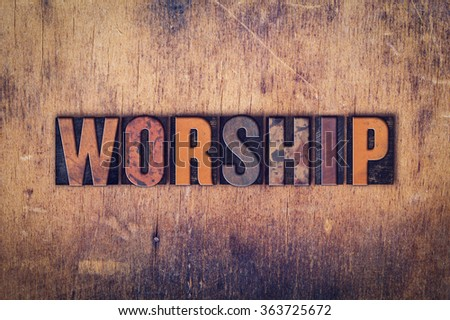 """The word """"Worship"""" written in dirty vintage letterpress type on a aged wooden background. - stock photo"""