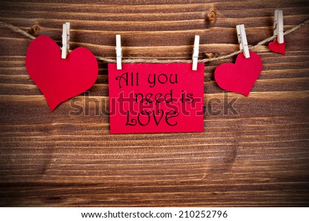 The Words All You Need is Love on a red Label with Hearts Hanging on a Line on Wooden Background - stock photo