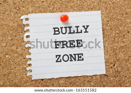 The words Bully Free Zone typed on a scrap of lined paper and pinned to a cork notice board. A concept for respect and tolerance in school and at work or home. - stock photo