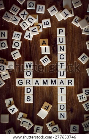 The words GRAMMAR, WORDS, and PUNCTUATION spelled  using letter tiles in the style of a crossword - stock photo