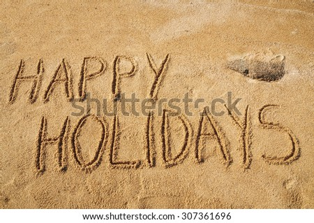 The words Happy Holidays written in the sand on the beach - stock photo