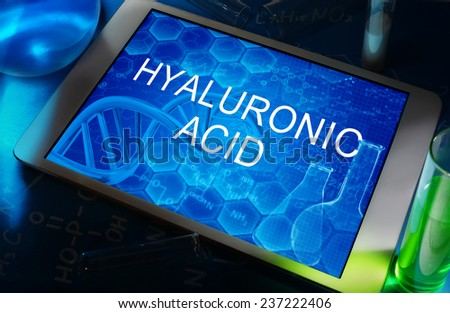 the words Hyaluronic acid on a tablet with test tubes   - stock photo