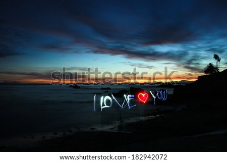 The words I Love You painted with light on a beach, after sunset. - stock photo