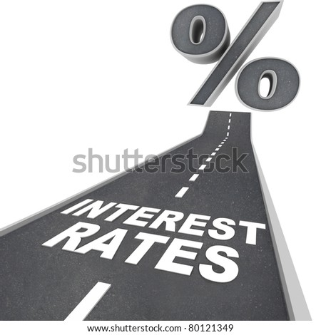 The words Interest Rates on a blacktop road and a percent sign at the top of the street, symbolizing the rising interest rates due to economic factors and conditions - stock photo