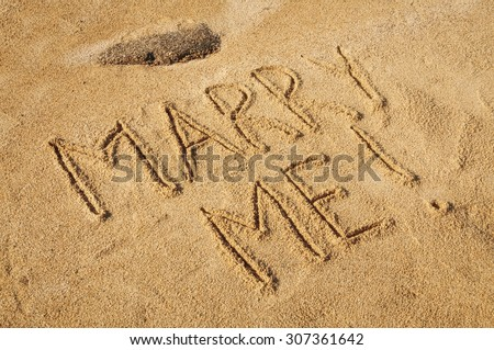The words Marry Me written in the sand on the beach - stock photo