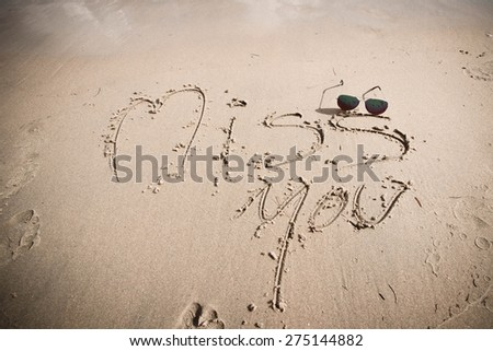 "The words ""Miss You"" drawn on a sandy beach with sunglasses on beach. - stock photo"